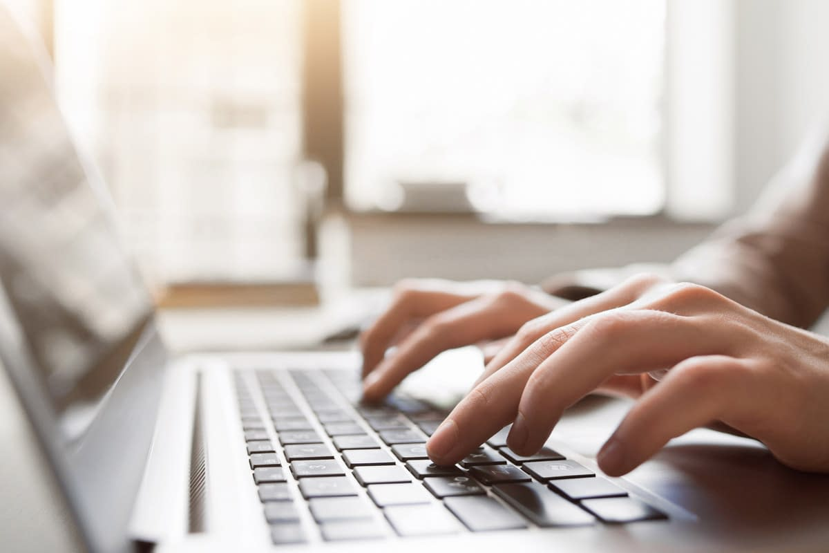 Person at laptop creating content for a website